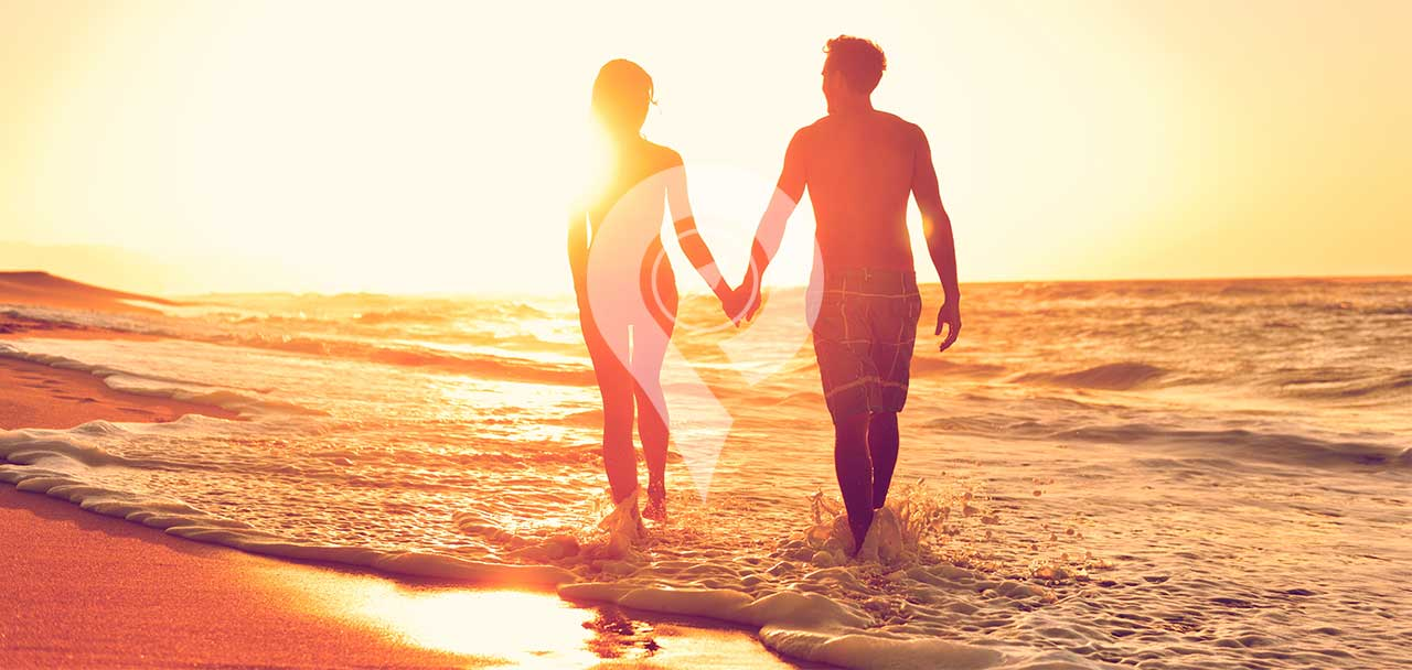 Tip-Top-V-Galapagos-Cruise-Honeymoon-Experience-Couple-on-Beach-Holding-hands-during-sunset