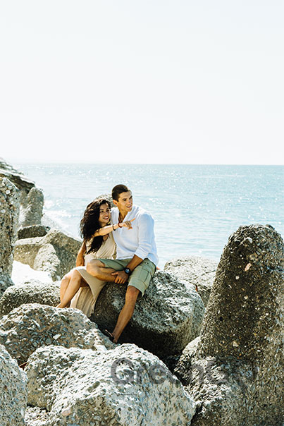 Tip-Top-V-Galapagos-Cruise-Honeymoon-Experience-Honeymoon-Couple-Sitting-on-rocks-at-Beach